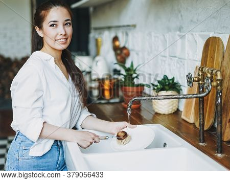 Young Woman Washes Dishes With Wooden Brush With Natural Bristles At Window In Kitchen. Zero Waste C
