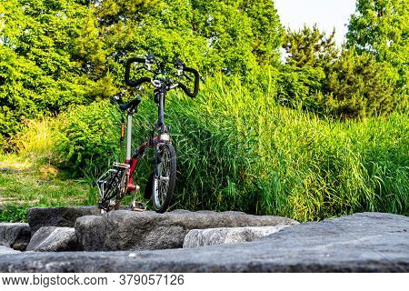 Geoje, South Korea - June 15, 2017: Brompton Folding Bike Park In Front Of The Small Stream In The S