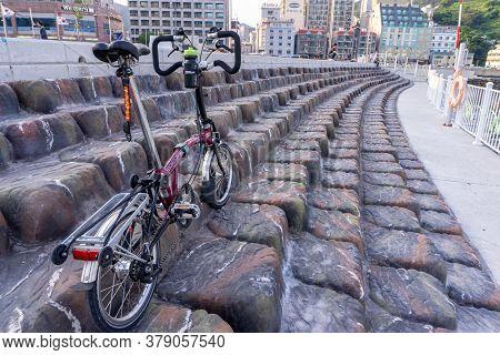 Geoje, South Korea - June 15, 2017: Brompton Folding Bike Parks On The Rock Step At The Public Park