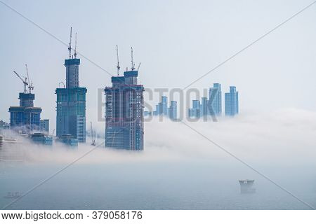 Thick Large And Heavy Mist Blow From The Sea To The Land And Pass Through Skyscrapers And Cover All