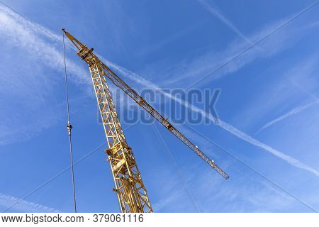 Planks On A Hook Of A Crane Under Blue Sky