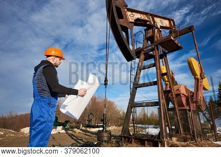 Side View Of Oil Worker Holding Plan Of Oil Field. Engineer In Work Uniform And Helmet Standing Near