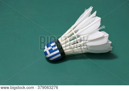 Used Shuttlecock And On Head Painted With Greece Flag Put Horizontal On Green Floor Of Badminton Cou