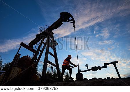 Silhouette Of Engineer In Work Vest And Helmet Working On Petroleum Pump Jack. Oil Worker Using Oil