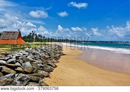 Summer, Beach, Ocean. Aquamarine Waves Leave A White Foam On The Yellow Sand. Stones Lie Along The S