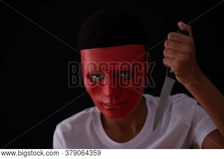 Ominous Looking Person Wearing A Mask With Knife In Hand