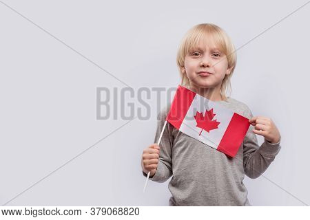 Young Fair-haired Boy Holding Flag Of Canada. Education In Canada.