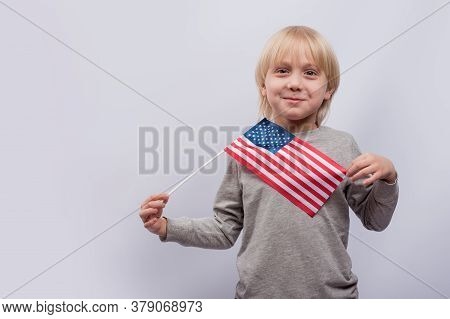 Exciting Fair-haired Boy Holding An American Flag On White Background. Education In America.