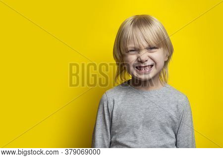 Fair-haired Boy Make Face. Portrait Of Blond Boy On Yellow Background. Copy Space.