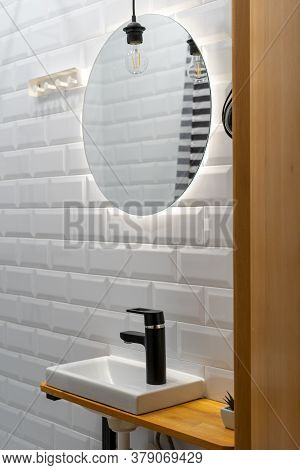 Vertical Photo Of White Bathroom In Modern Apartment With Mirror, Sink And Black Water Tap Against T