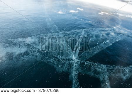 Ice Texture Close-up. Frozen Baikal Lake In Siberia. Beautiful Cracked Ice With Air And Methane Bubb