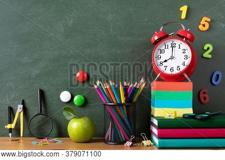 Back To School Or Education Concept With Alarm Clock, Green Apple And School Supplies Against Blackb