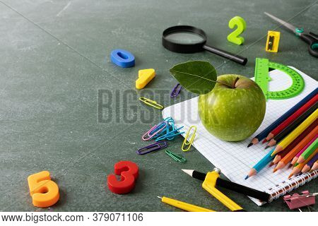 Back To School And Education Concept With Colorful Stationery Supplies And Green Apple On Blackboard