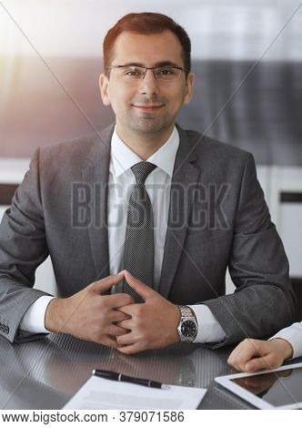 Businessman Headshot At Meeting In Modern Office. Entrepreneur Sitting At The Table With Colleagues.