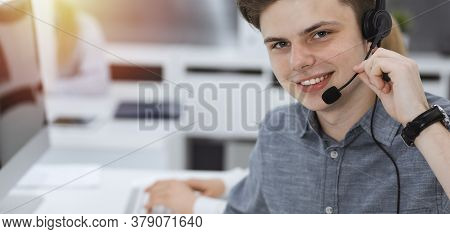 Call Center. Group Of Casual Dressed Operators At Work. Businessman In Headset At Customer Service O