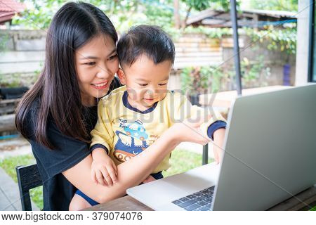 Smart Young Asian Mom Hold Baby Boy Use Laptop Computer In Cafe
