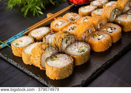 Set Of Fried Sushi Rolls With Wasabi And Ginger On Black Background. Japanese Oriental Cuisine