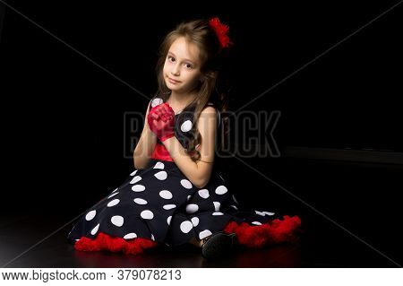 Beautiful Girl In A Polka-dot Dress, Red Gloves And A Bow Sits On The Floor And Looks Away, Portrait
