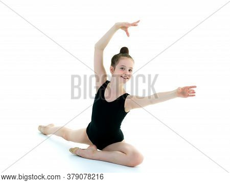 A Girl Gymnast Performs An Acrobatic Element On The Floor. The Concept Of Childhood, Sport, Healthy