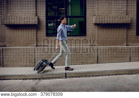 Hurrying To Get On A Business Trip. Stressed Passenger Businessman Walking With Suitcase In The City