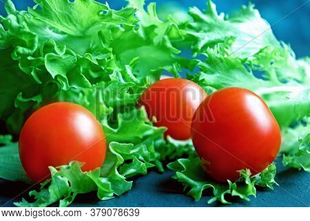 Cherry Tomatoes And Lettuce Lie On A Dark Surface. Ripe Cherry Tomatoes. Tomatoes Are On The Table.