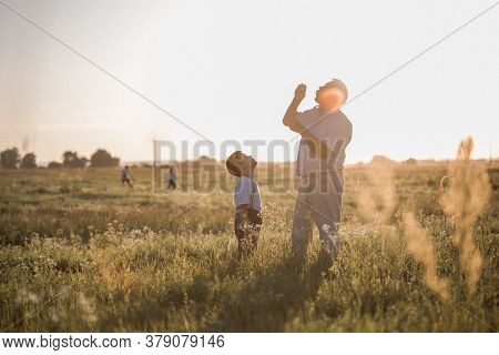 Grandfather And Grandson. Happy Senior Man Grandfather With Cute Little Boy Grandson Playing In Fiel