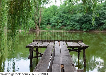 Old Wooden Pier On The Lake On The Background Of The Forest. Summer Warm Evening. Nature Getaway And