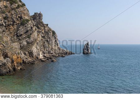 Rock Sail, Yalta, Southern Coast Of Crimea. A Sailing Yacht Sails Next To A Rocky Shore On A Sunny S