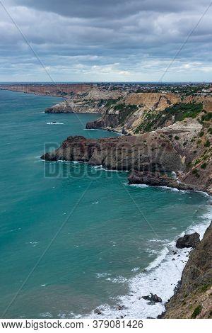 Calm Azure Sea And Rocky Seashore. View Of The Black Sea Coast In Crimea, Cape Fiolent, Russia. Vert