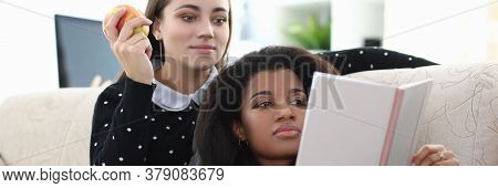 Portrait Of Beautiful Lady And Woman Of African Appearance Looking At Book With Interest And Gladnes