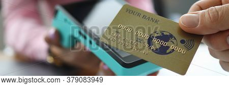 Close-up Of Hand Holding Gold Credit Card. Person Paying For Service Or Product. Female Worker Givin