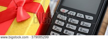 Close-up Of Terminal Machine And Yellow Present Box With Red Bow On Top. Spending Money On Online Sh