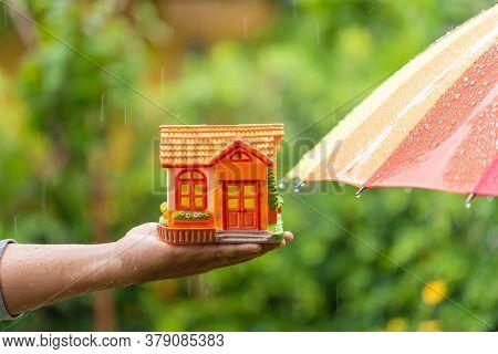 Hand Holding Piggy Bank (home Model) Beside Wet Umbrella In Rainy Days On Green Nature Blur Backgrou