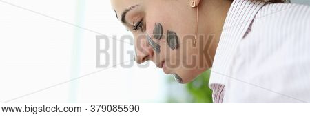 Close-up Of Young Female With Clay Mask On Face. Attractive Woman In Pyjamas After Night Sleep. Copy