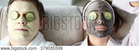 Top View Of Wife And Husband Wearing Cleaning Face Masks. Relaxed Woman And Man Laying On Sofa. Coup
