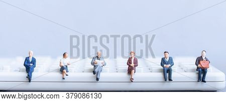 Miniature People: Elderly People Sitting On Calculator. Social Security Income And Pensions. Money S