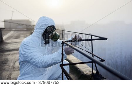 Laboratory Guy Is Working With A Railing On The Roof In The Morning, Wearing Protective Outfit And G
