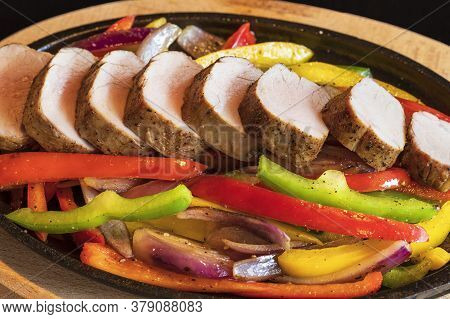 Close-up Of Roasted Pork Tenderloin - Medallions With Grilled Vegetables On A Hot Pan. The Food Is I