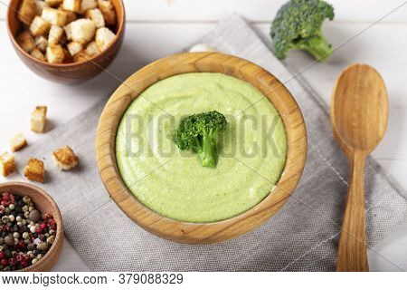 Green Broccoli Cream Vegetable Soup In A Wooden Plate On The Table. Soup Decorated With Broccoli Inf