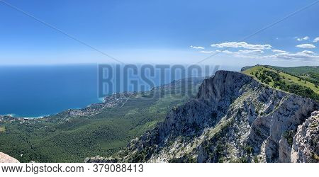 View From The Height Of The Mountains, Cliff, Rocks, The Bottom Of The City Among Green Vegetation,