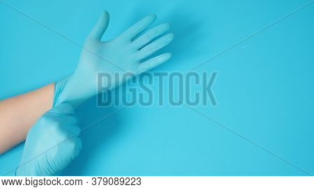 The Hand Is Pulling Doctor Gloves Or Blue Latex Gloves Of Right Hand On Blue Background.