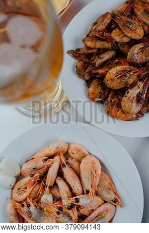 Boiled Shrimps On A White Plate, Fried Shrimps On A White Plate And A Glass Of Beer On A Light Backg