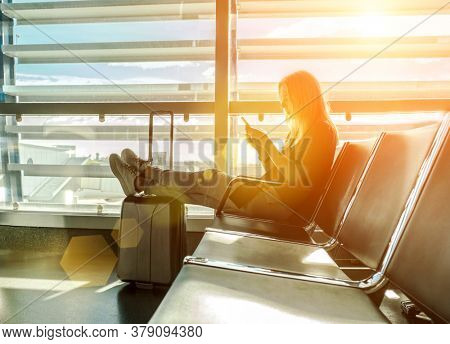 Woman waiting aircraft in airport. Young Female tourist traveling using her smartphone device. Online registration in mobile application.