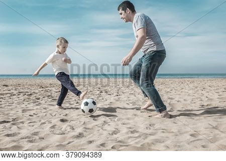 Father and son playing in football on sea coastline beach under sun light in sunny day. Holidays, Sport, Family concept.