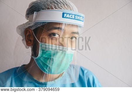 Portrait Of Doctor Having Tired From Work While Wearing Ppe Suit For Protect Coronavirus Disease. Th