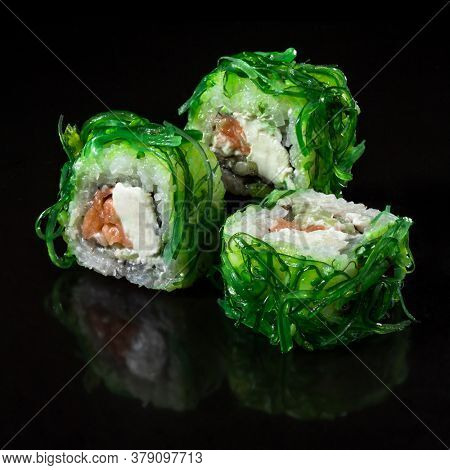 Imperator Sushi roll with seafood and Chuka. Sushi roll with Chuka, salmon, cucumber, and cream chease over  black backgraund.