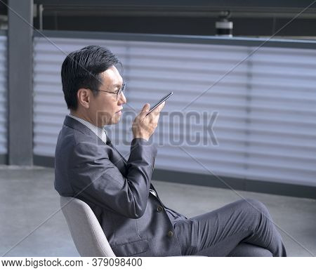 Chinese Businessman Using Cellphone To Leave Voice Message. Copy Space.