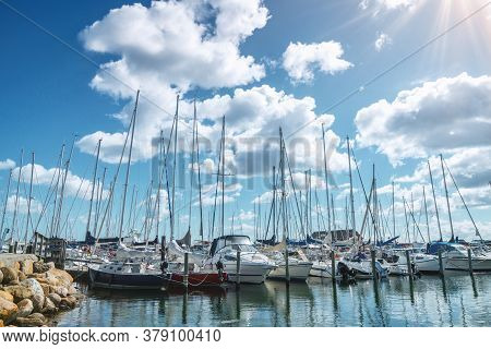 Sailing Boats In A Marine Harbor In The Summer With The Sun Shining From A Blue Sky