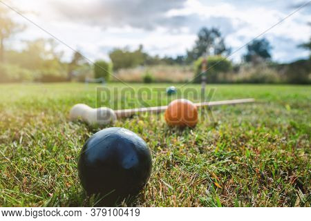 Croquet Outdoor Game On A Lawn In The Summer With A Mallet And Colorful Balls