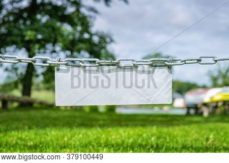 Blank Metal Sign Hanging On A Chain Over A Green Lawn With Boats And A Lake In The Background